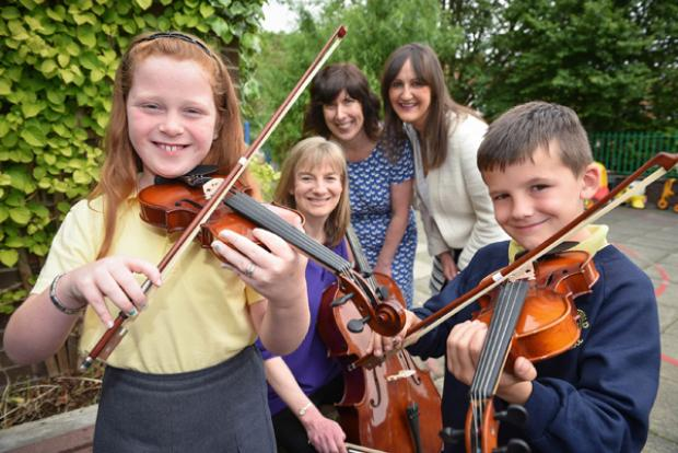 Pupils from Wheatfield Primary School in North Belfast show off their new skills with Morag Stewart, Principal Cello and facilitator of from the Ulster Orchestra Crescendo project, Maxine Hume, Principal of Wheatfield Primary School and Linsey Farrell, Programme Director, Urban Villages Initiative.