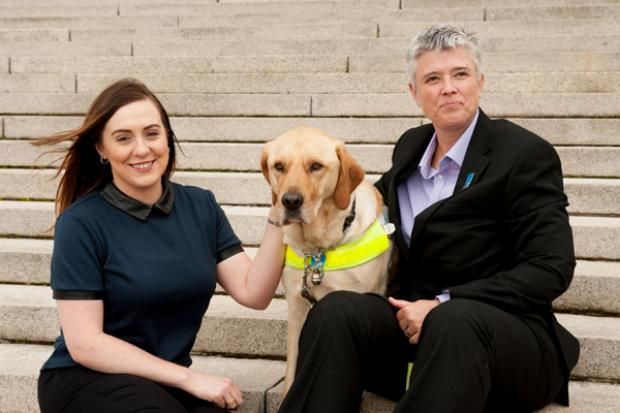 Junior Minister, Megan Fearon with Diane Marks and her quide dog Morris outside Parliament Buildings.