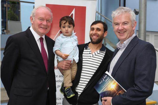 The deputy First Minister, Martin McGuinness and Glenn Jordan,Director, Law Centre (NI), with Syrian refugees Sorani Mohamed and son, Nouraedin (14 months)